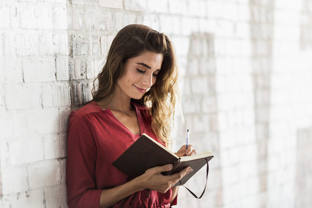 A photo of smiling businesswoman writing in diary. Beautiful young female standing against white wall. She is wearing smart casuals at office.